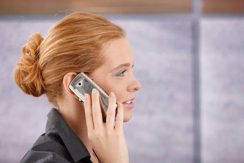 Ritratto di vista laterale della testarossa sul telefono fotografia stock