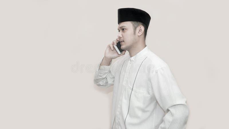 Ritratto di vista laterale di un uomo musulmano asiatico facendo uso dello smartphone che prende una chiamata fotografia stock libera da diritti