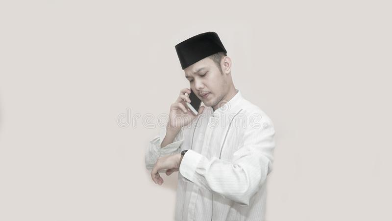 Ritratto di vista laterale di un uomo musulmano asiatico facendo uso dello smartphone che prende una chiamata immagine stock