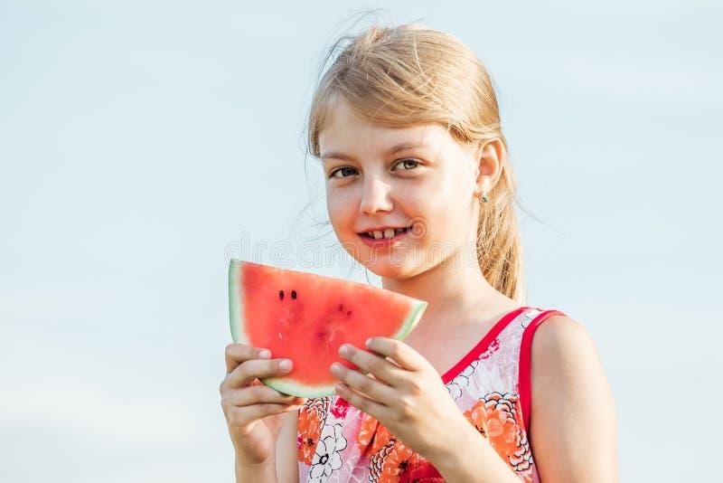 Ritratto divertente della bambina bionda adorabile che mangia anguria fotografia stock