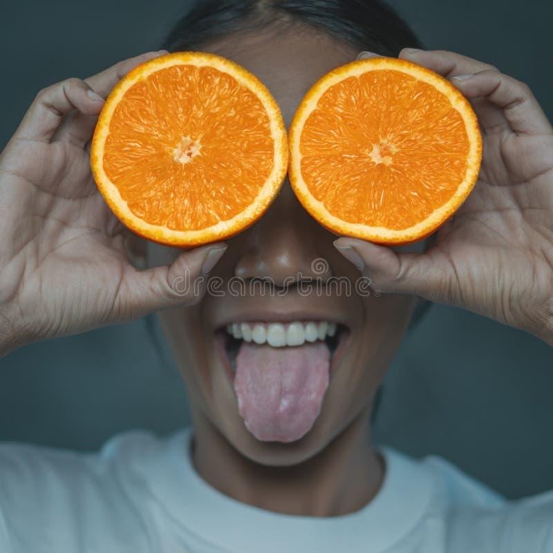 Ritratto divertente della lingua di rappresentazione della giovane donna fuori mentre coprendo i suoi occhi di metà dell'arancia fotografia stock libera da diritti