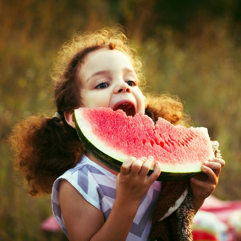 Ritratto divertente di bambina dai capelli riccia incredibilmente bella che mangia anguria, spuntino sano della frutta, bambino a immagini stock