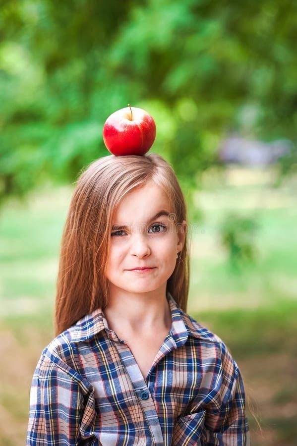 Ritratto divertente di bella neonata con una mela rossa sulla sua testa Una ragazza in una camicia di plaid su un'azienda agricol immagini stock libere da diritti