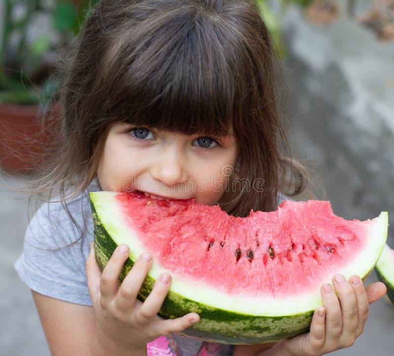 Ritratto divertente di occhi azzurri incredibilmente bei di una bambina, mangiante anguria, spuntino sano della frutta, fotografia stock libera da diritti