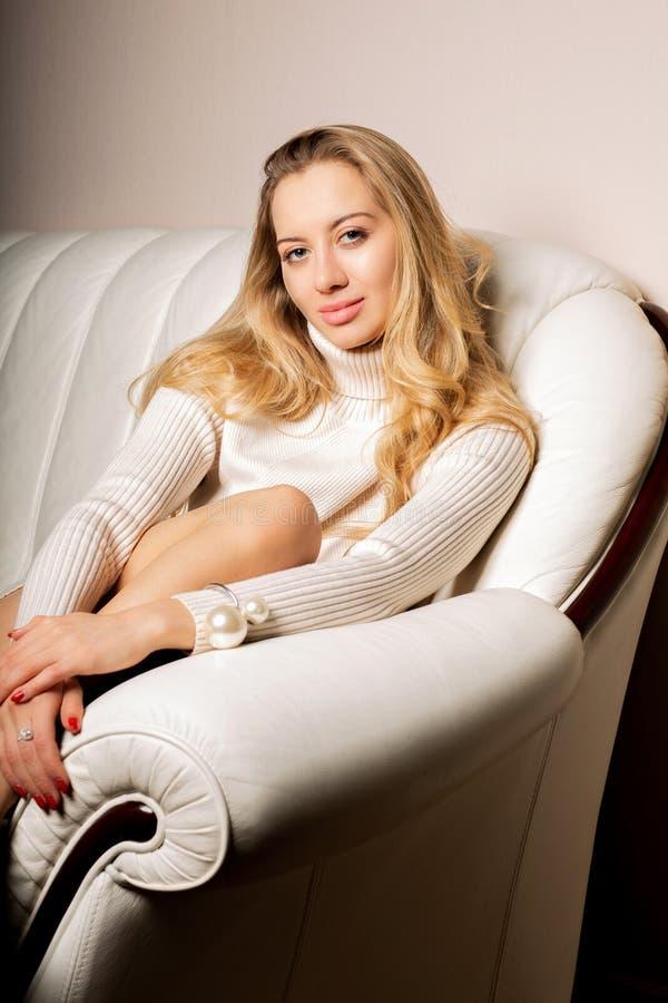 Ritratto domestico di stile di vita del maglione d'uso della bella donna, rilassantesi sul sofà al salone fotografie stock libere da diritti