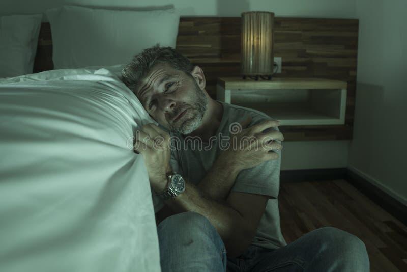 Ritratto domestico drammatico di giovane uomo solo disperato e depresso che si siede sul pavimento della camera da letto che grid fotografia stock libera da diritti