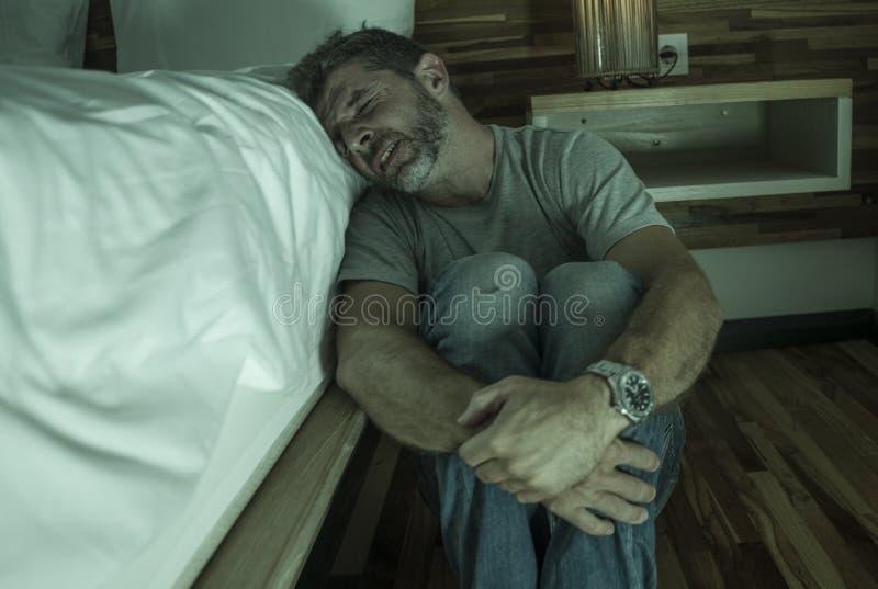 Ritratto domestico drammatico di giovane uomo solo disperato e depresso che si siede sul pavimento della camera da letto che grid immagini stock libere da diritti