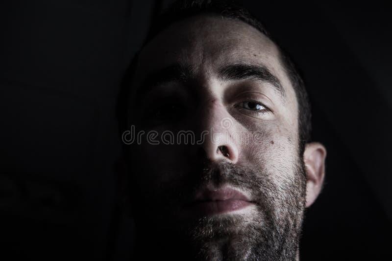 Ritratto drammatico di mezzo fronte inespressivo del giovane in dee fotografia stock libera da diritti