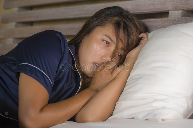 Ritratto drammatico di stile di vita di giovane donna asiatica triste e depressa attraente in pigiami che si trovano a letto nell immagini stock libere da diritti