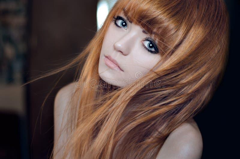 Ritratto drammatico di un tema della ragazza: ritratto di bella ragazza con i capelli di volo nel vento contro un fondo nello stu fotografia stock