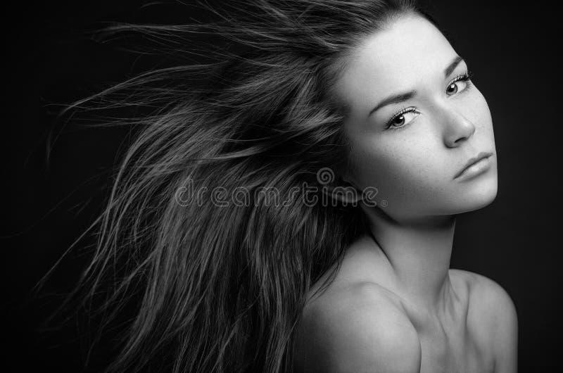 Ritratto drammatico di un tema della ragazza: ritratto di bella ragazza sola con i capelli di volo nel vento isolato su fondo scu fotografia stock libera da diritti