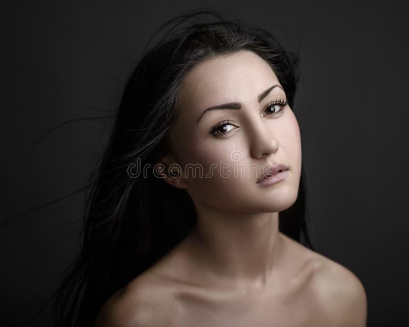 Ritratto drammatico di un tema della ragazza: ritratto di bella ragazza sola con i capelli di volo nel vento isolato su fondo scu fotografie stock