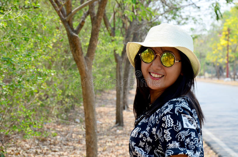 Ritratto e gioco tailandesi della donna ad all'aperto con l'albero accanto alla strada immagine stock libera da diritti