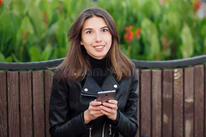Ritratto emozionale di giovane donna castana sorridente graziosa che si siede all'aperto il parco della città che porta cappotto  immagine stock libera da diritti