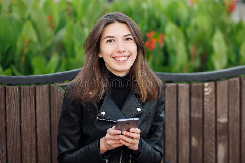 Ritratto emozionale di giovane donna castana sorridente graziosa che si siede all'aperto il parco della città che porta cappotto  fotografia stock libera da diritti