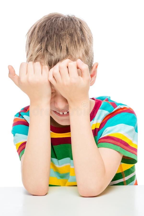 ritratto emozionale di un ragazzo di 10 anni alla tavola su un fondo bianco fotografia stock