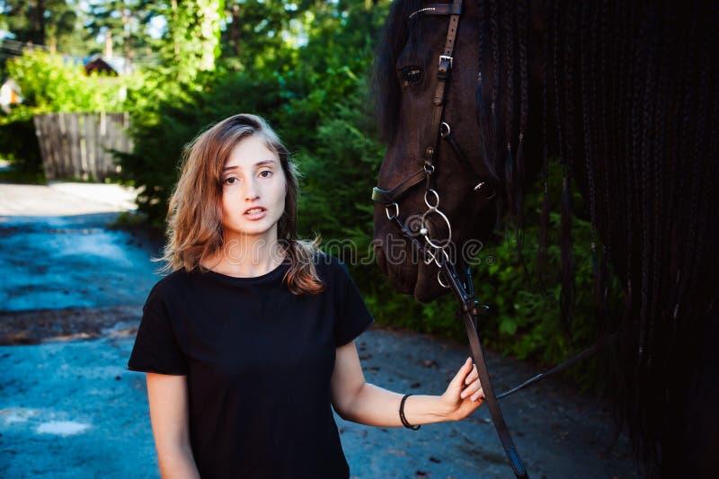 Ritratto emozionale di una femmina nell'amore con i cavalli, animale domestico frisone nero del purosangue dello stallone fotografie stock libere da diritti