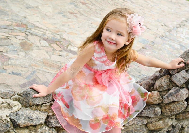 Ritratto esterno della bambina di seduta sveglia immagini stock libere da diritti