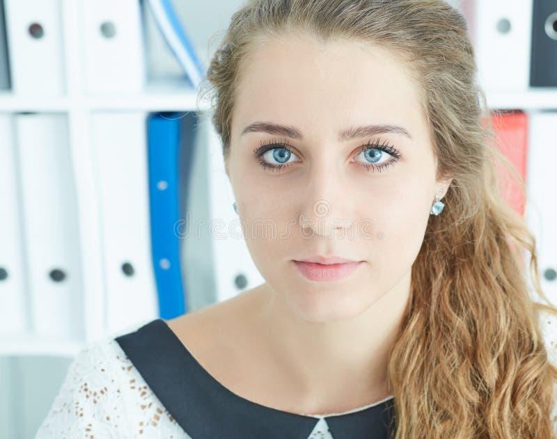 Ritratto facciale del primo piano di giovane segretario caucasico attraente sul fondo dell'ufficio immagini stock libere da diritti