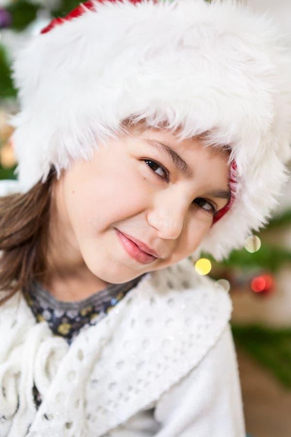 Ritratto facciale della ragazza pre-teenager in cappello bianco di Santa al Natale fotografia stock