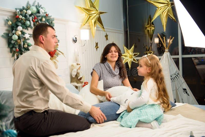 Ritratto felice della famiglia sul Natale, sulla madre, sul padre e sul bambino sedentesi sul letto a casa, decorazione di chritm fotografia stock