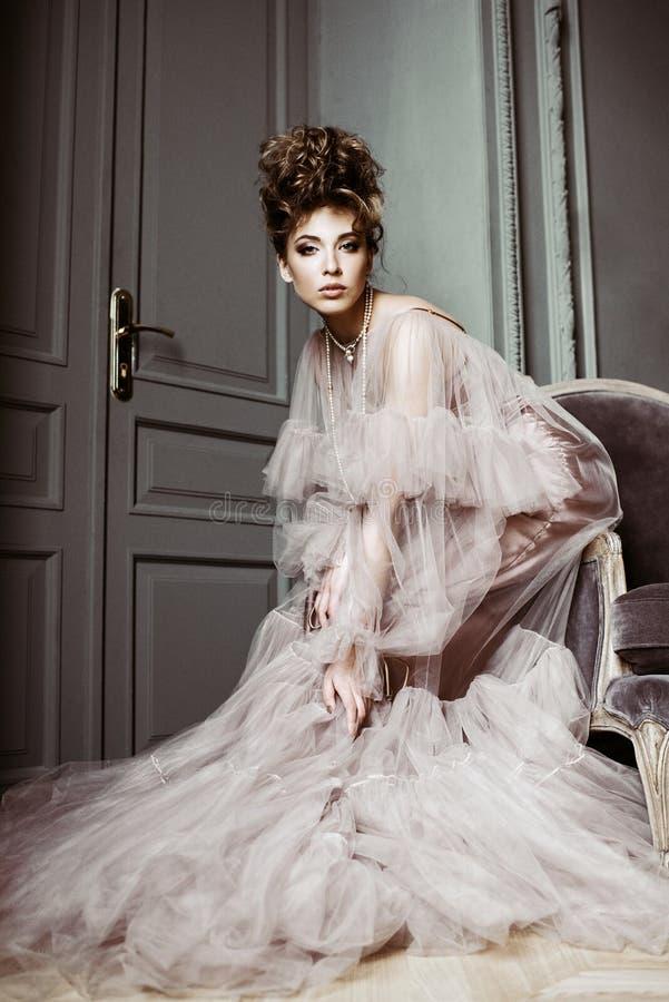 Ritratto femminile alla moda di signora sveglia in vestito rosa all'interno immagine stock