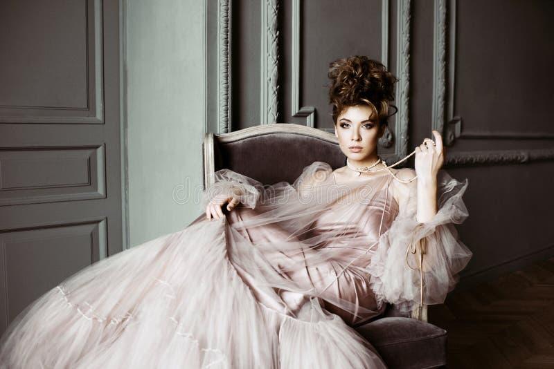 Ritratto femminile alla moda di signora sveglia in vestito rosa all'interno fotografie stock libere da diritti