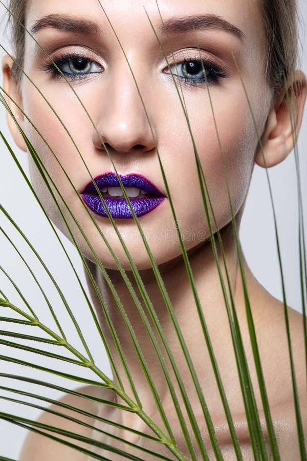 Ritratto femminile con le foglie del ramo della palma su priorità alta e trucco del fronte di bellezza con le labbra viola fotografia stock libera da diritti