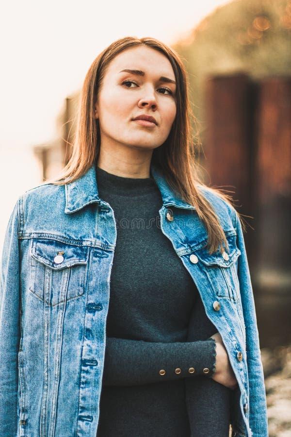 Ritratto giovane della ragazza bionda caucasica attraente, snella, bella in un rivestimento dei jeans La ragazza sorridente gode  fotografie stock