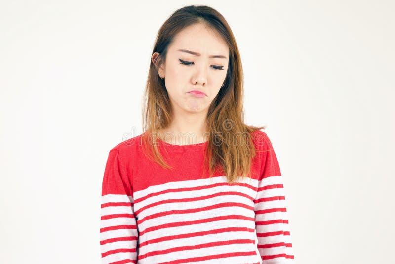 Ritratto grazioso della ragazza asiatica in studio che sembra triste e che aggrotta le sopracciglia fotografia stock libera da diritti