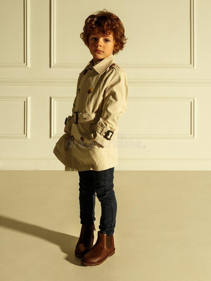 Ritratto grazioso di un ragazzino riccio in abbigliamento alla moda, con le mani in sua tasca, isolata su un fondo beige fotografie stock