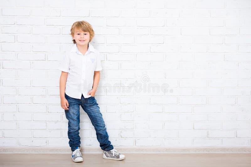 Ritratto integrale del ragazzino sveglio che posa sopra il bianco fotografia stock libera da diritti