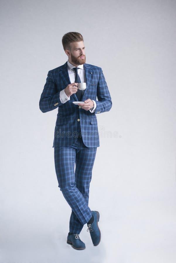 Ritratto integrale dell'uomo barbuto elegante vago attraente serio in vestito pieno che odora l'aroma di caffè amaro fresco immagine stock libera da diritti