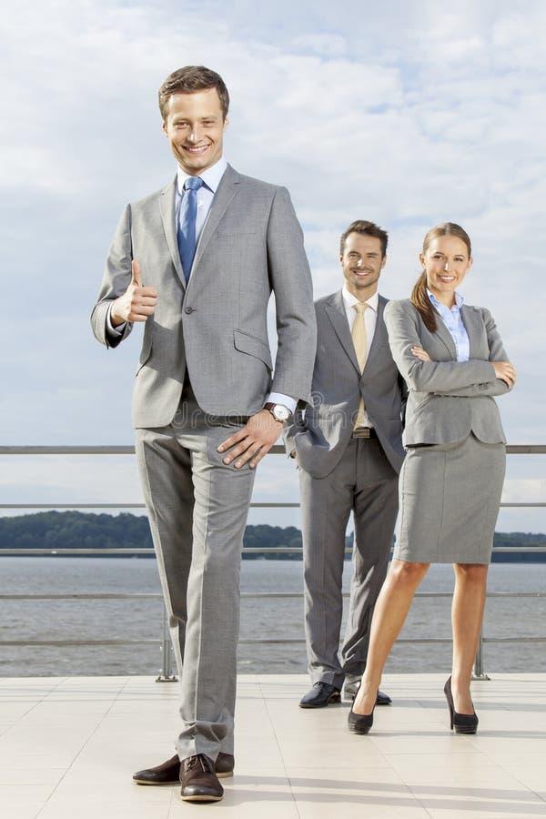Ritratto integrale dell'uomo d'affari sicuro che gesturing i pollici su mentre stando con i colleghe sul terrazzo contro il cielo fotografie stock libere da diritti