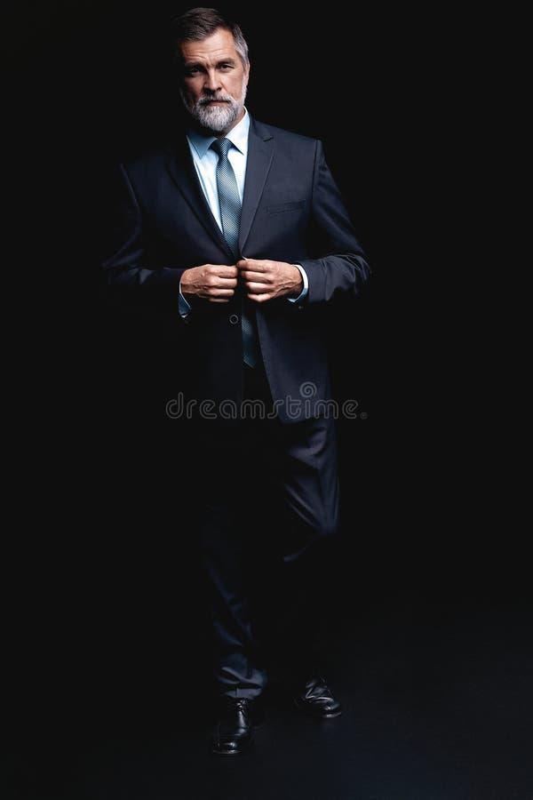 Ritratto integrale dell'uomo di affari maturi che indossa condizione convenzionale del vestito sul fondo nero immagini stock