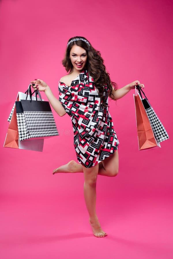 Ritratto integrale della donna felice che tiene sacchetto della spesa di carta in mani e che salta, posando alla macchina fotogra immagini stock libere da diritti