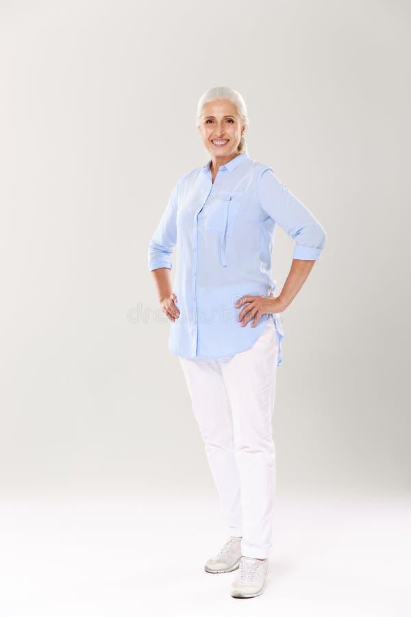 Ritratto integrale della donna matura allegra in camicia blu e fotografia stock