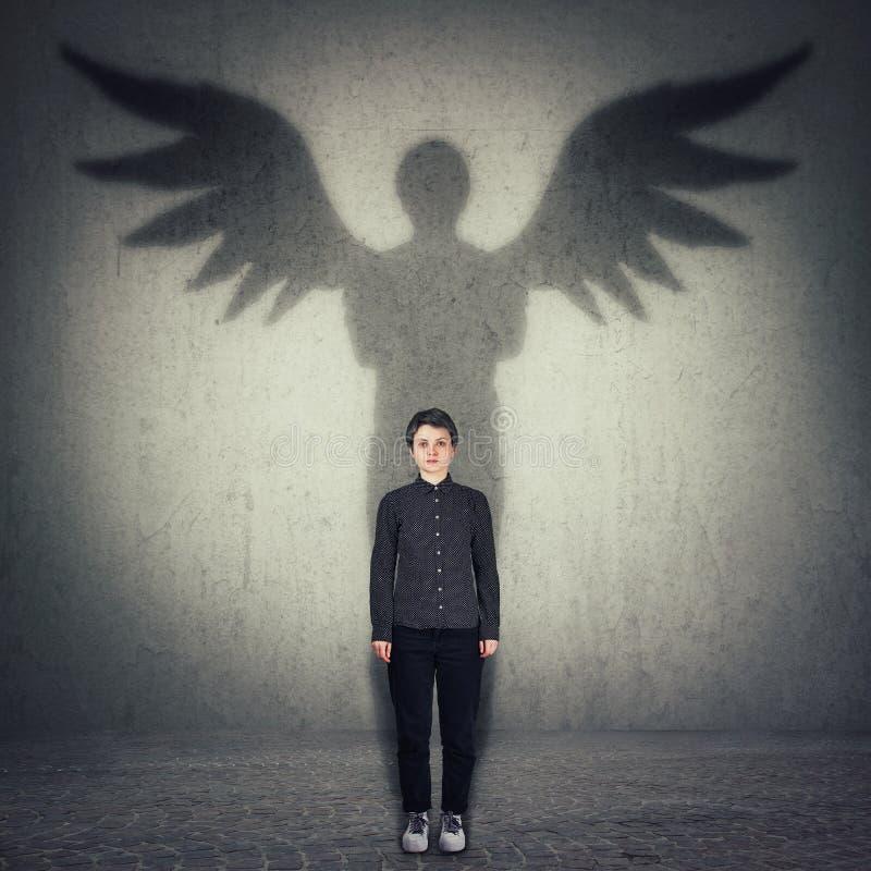 Ritratto integrale della donna sicura casuale che getta un'ombra del supereroe con le ali di angelo su una parete della stanza sc immagine stock