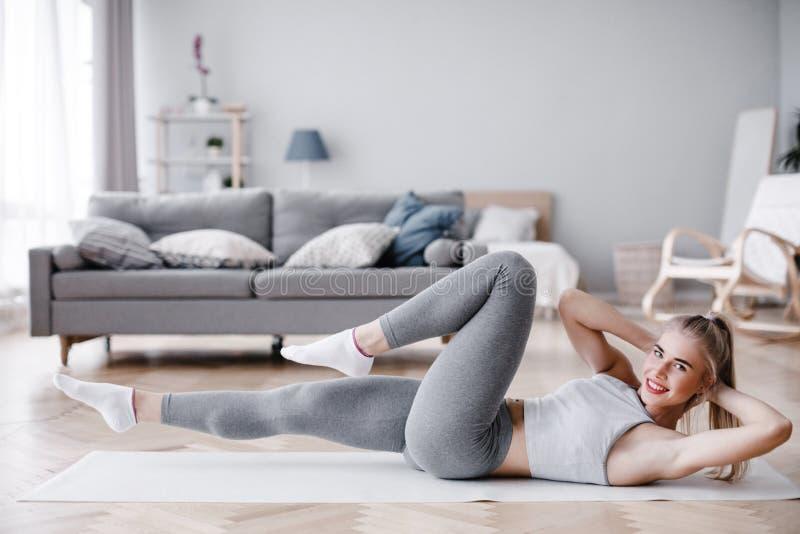 Ritratto integrale della giovane donna attraente che risolve a casa, facendo allungando gli esercizi o esercizio dei pilates sull immagine stock