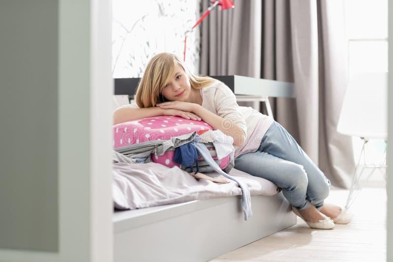 Ritratto integrale della ragazza che si rilassa sulla valigia di gonfiamento a casa immagine stock libera da diritti