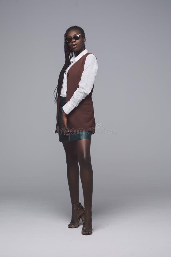 Ritratto integrale della ragazza di modello africana di modo isolato su fondo grigio Donna alla moda di bellezza che propone prod fotografia stock