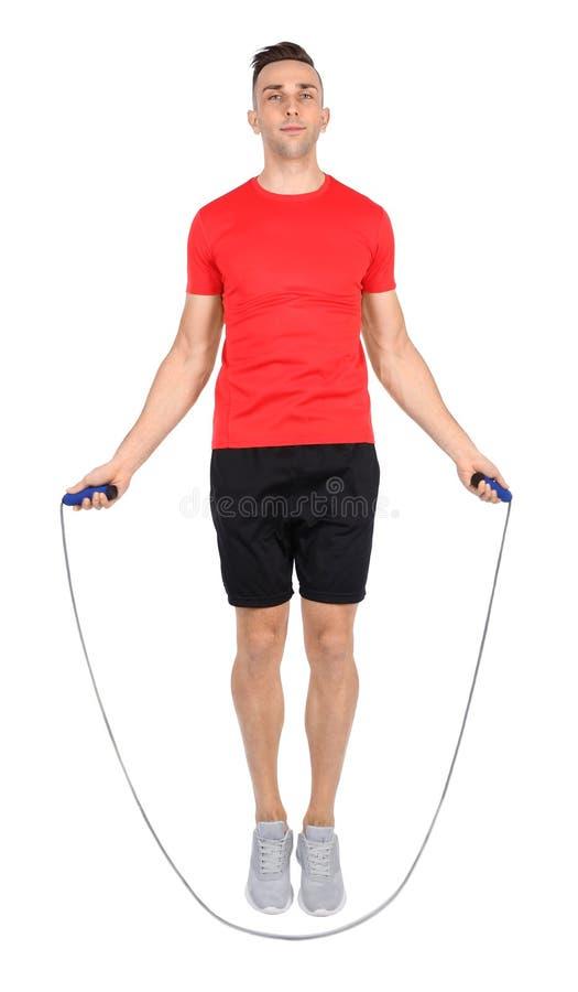 Ritratto integrale di giovane addestramento allegro dell'uomo con la corda di salto su bianco fotografia stock