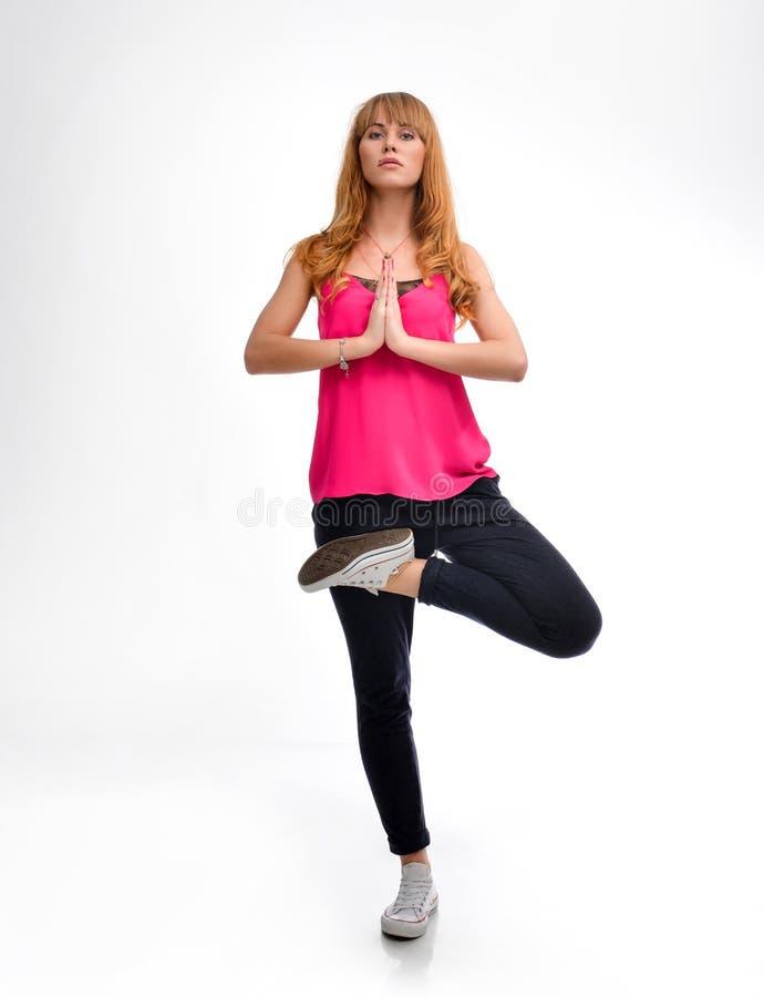 Ritratto integrale di giovane modello dai capelli rossi di forma fisica in abiti sportivi rosa che fanno esercizio dei pilates o  fotografie stock