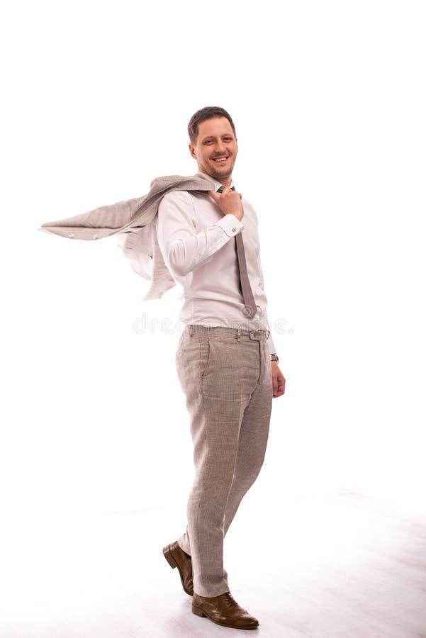 Ritratto integrale di un giovane che indossa vestito beige, isolato Cammina sorridere e tiene il suo rivestimento sopra la sua sp fotografia stock libera da diritti