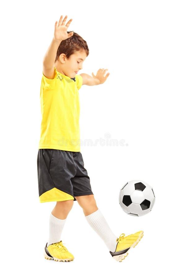 Ritratto integrale di un ragazzo in abiti sportivi sedere scuotenti lievemente di un calcio fotografia stock