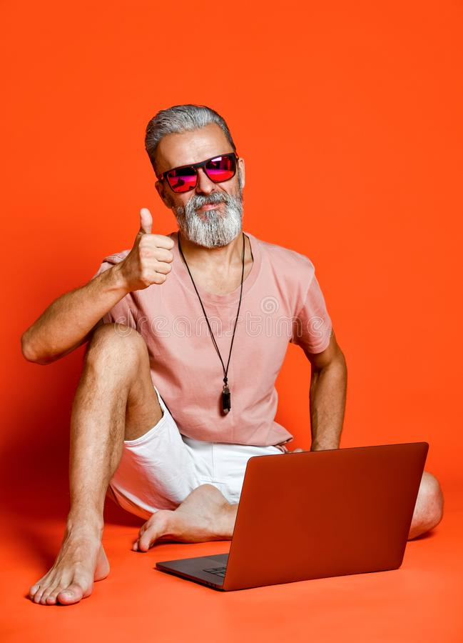 Ritratto integrale di un uomo anziano felice che per mezzo del computer portatile isolato sopra fondo arancio fotografia stock libera da diritti