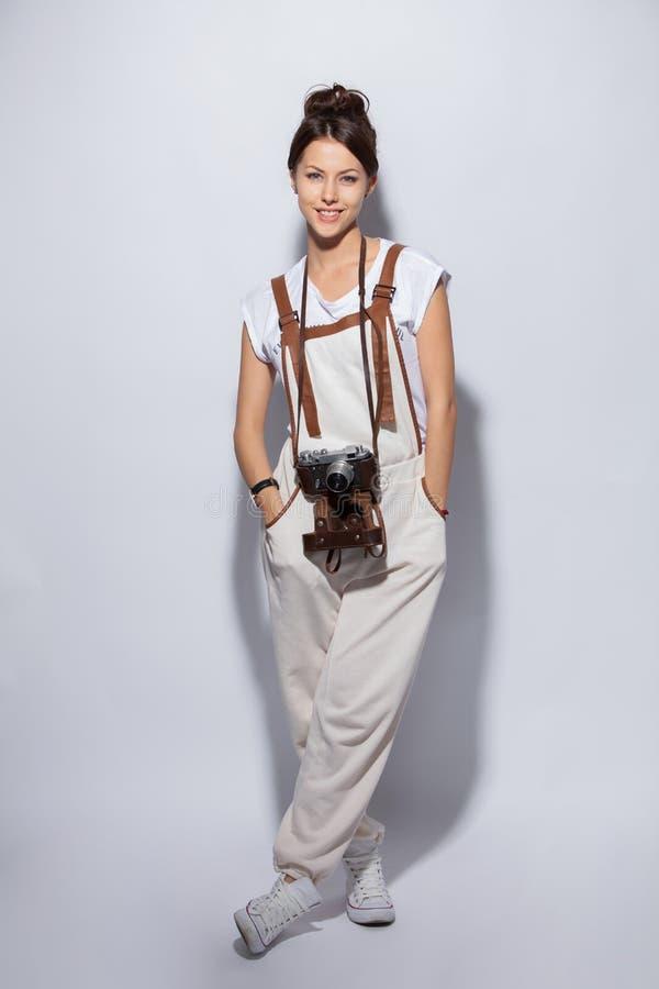 Ritratto integrale di una condizione casuale sorridente della donna sul fondo bianco e di esame della macchina fotografica fotografia stock libera da diritti