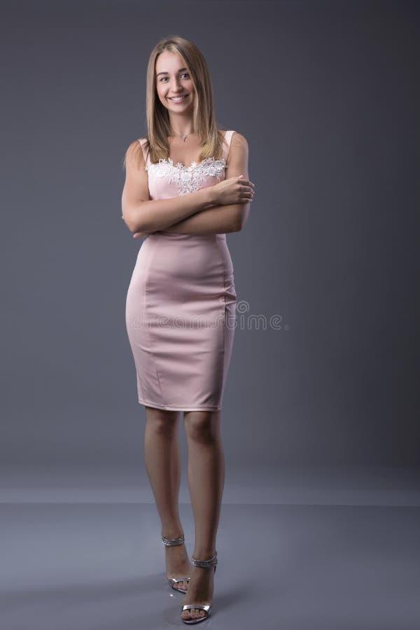 Ritratto integrale di una donna bionda sexy in vestito da modo con le mani sulle anche Fondo grigio Concetto di linguaggio del co immagini stock