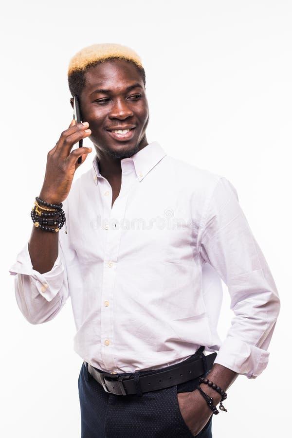 Ritratto isolato dei vetri d'uso del giovane ed uomo afroamericano bello e di un vestito che parla su un telefono e su un sorride immagini stock libere da diritti