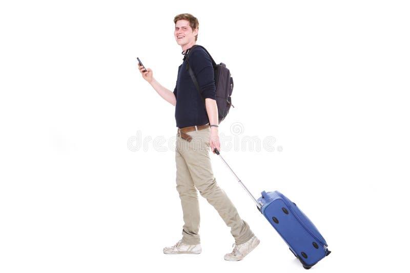 Ritratto laterale del giovane con la valigia ed il telefono cellulare su fondo bianco isolato fotografie stock